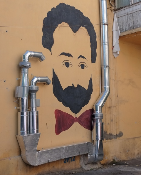 yerevan street art, man's head, black hair and beard, red bow tie, on yellow wall