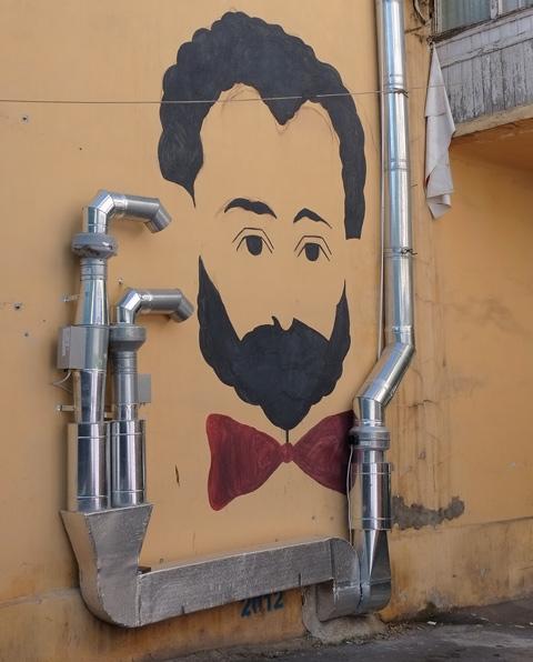 yerevan street art, man's head, black hair and beard, red bow tie, on yellow wall