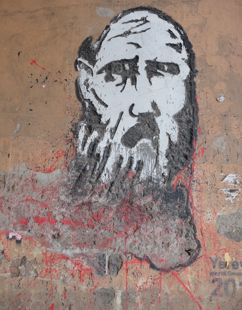 yerevan street art, man's head, black hair and beard and moustache, wild eyes, on concrete that is crumbling a bit