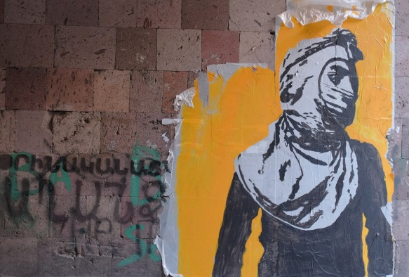 paste up of a person in black and white, hood and mask, yellow background