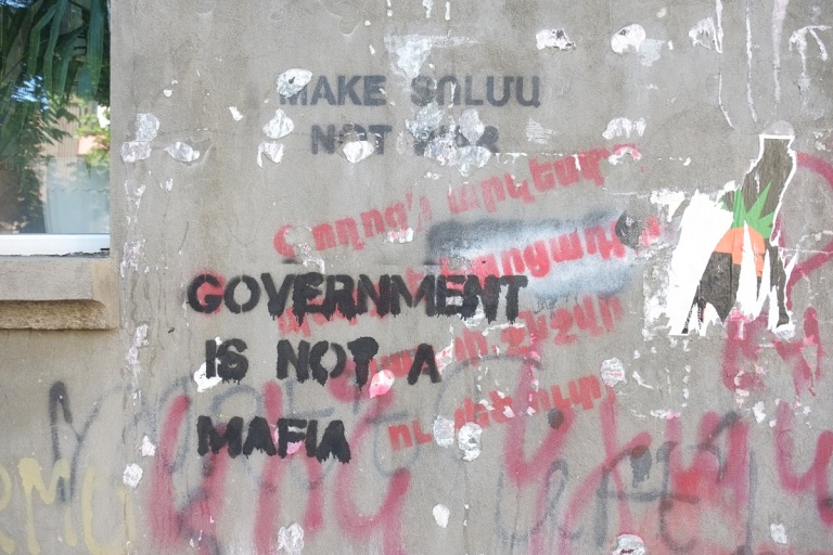 word stencils on top of each other on a wall, one in black says Government is not a mafia, red words in Armenian