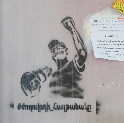 black stencil of a man holding a megaphone in one hand and with the other hand raised in a fist, words in Armenian written below it.