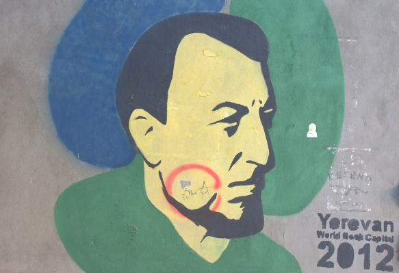 yerevan street art, man's head, in profile, black hair, beard, with yellowish face, words say Yerevan World Book Capital 2012