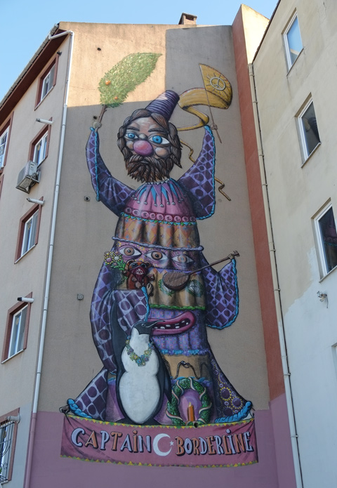 large mural in Kadikoy Istanbul, a man, clownish features, black bears, standing up,