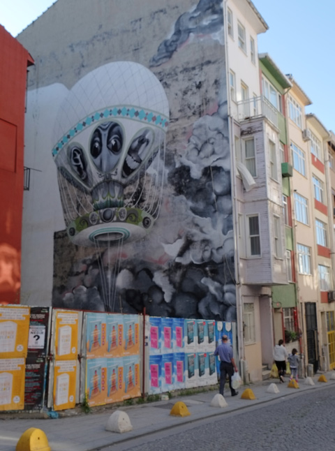 large mural in Kadikoy on the side of a building, hot air balloon, on the side of a building, vacant lot beside behind hoardings covered with ad posters Painted by Brazilian artist Claude Ethos