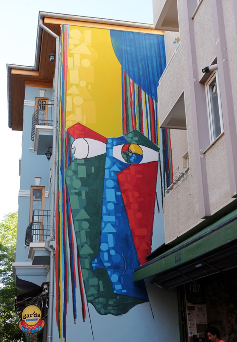 large mural in Kadikoy of an abstracted face in yellow, blue, red, and green, eyes looking out onto the street