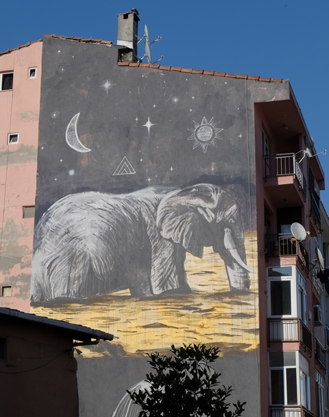 a large mural of a realistic looking elephant at night, in grey tones, moon and stars too