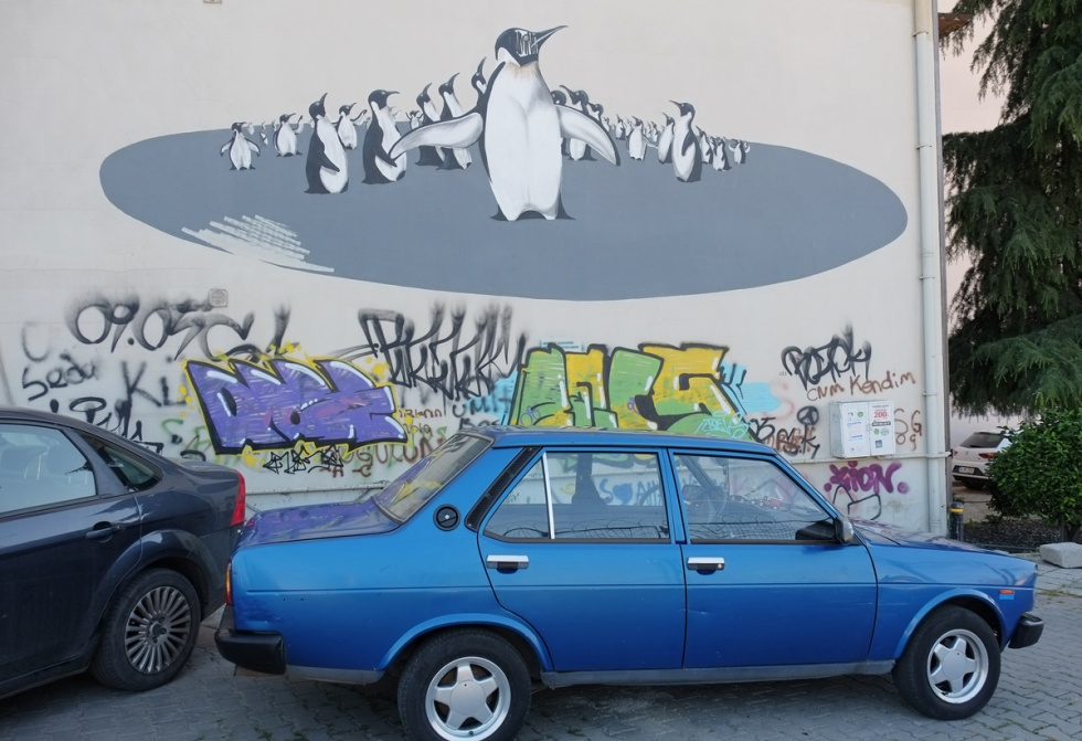 a small blue car is parked in front of the bottom part of a large mural in Kadikoy Istanbul, a group of penguins on top and some text street art on the bottom