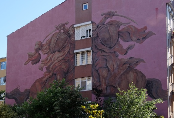 large purple hued mural in Kadikoy, two horsemen facing each other with a column of windows in the middle, by Argentinian artis Jaz