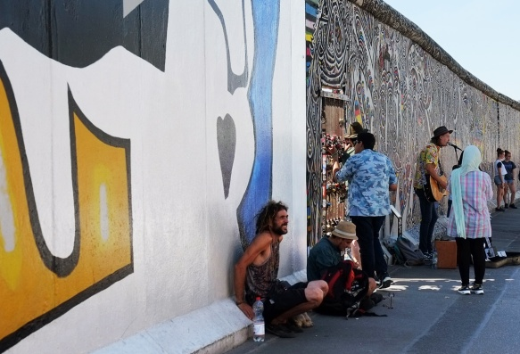 people hanging out in front of part of a mural on Berlin Wall, Eastside gallery
