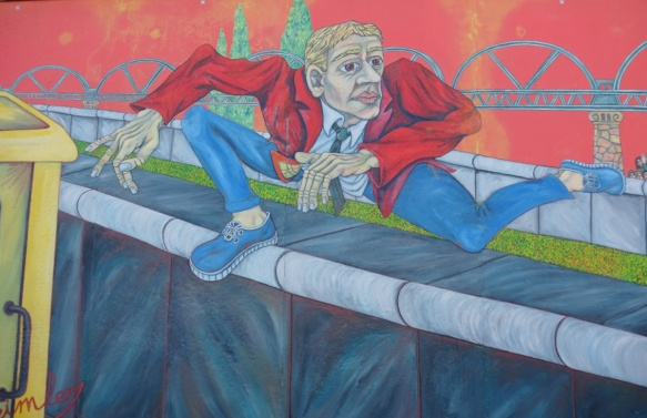 part of a mural on Berlin Wall, Eastside gallery, a man in a red jacket jumps over the Berlin wall