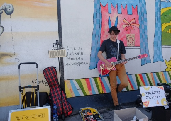 a young man playing a guitar in front of part of a mural on Berlin Wall, Eastside gallery