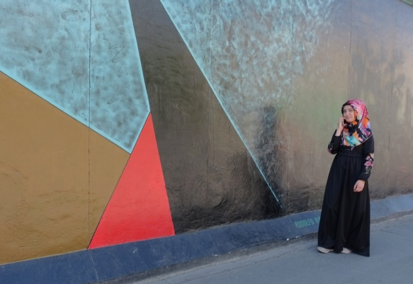 a young muslim woman in a head scarf walks past part of a mural on Berlin Wall, Eastside gallery