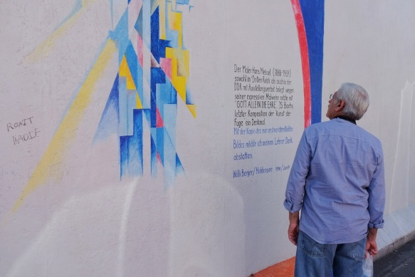 a man stops to look at part of a mural on Berlin Wall, Eastside gallery, tribute to painter Hans Meissel by Willi Berger