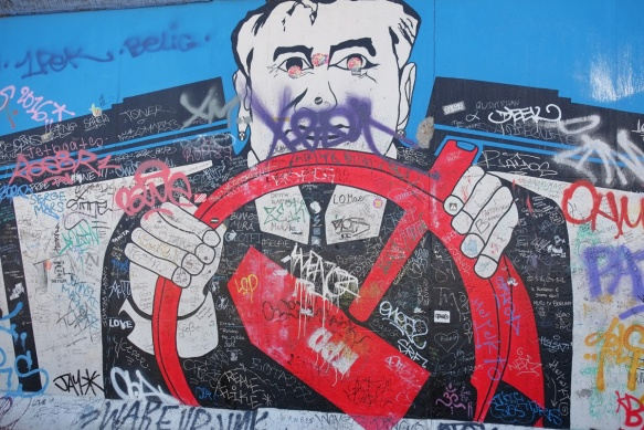 part of a mural on Berlin Wall, Eastside gallery, picture of Mikhail Gorbechev driving a car with a hammer and sickle shaped steering wheel.