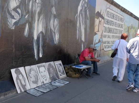 a man sells black and white drawn portraits in front of part of a mural on Berlin Wall, Eastside gallery