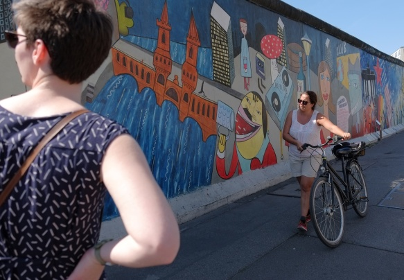 a woman walks her bike past part of a mural on Berlin Wall, Eastside gallery