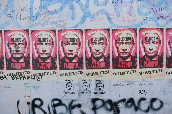 part of a mural on Berlin Wall, Eastside gallery - posters with the face of Putin, Russin leader, with words, Bloody Vladimir, wanted poster