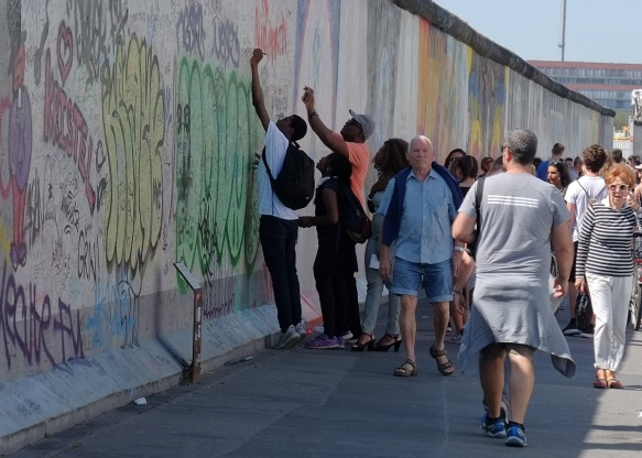 people reaching up high to write things on the wall, part of a mural on Berlin Wall, Eastside gallery