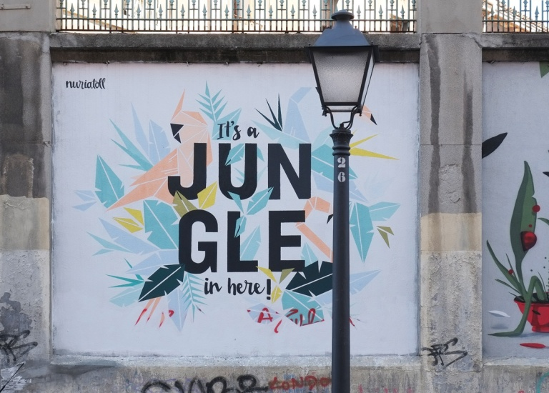 lampost in front of square mural, Madrid, muros tabacalera, words that say It's a jungle in here, pale coloured leaves and birds behind the words