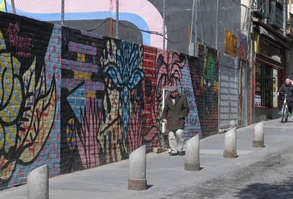 a man walks down a street in Madrid, beside a low brick wall that has been covered with street art murals