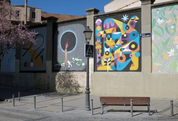 Calle de Miguel Servet, concrete wall with murals on it, bench in front of it, tree with pink blossoms