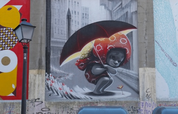 mural of a small girl huddled under an umbrella, grey tone city scape behind her, some small flowers on the ground