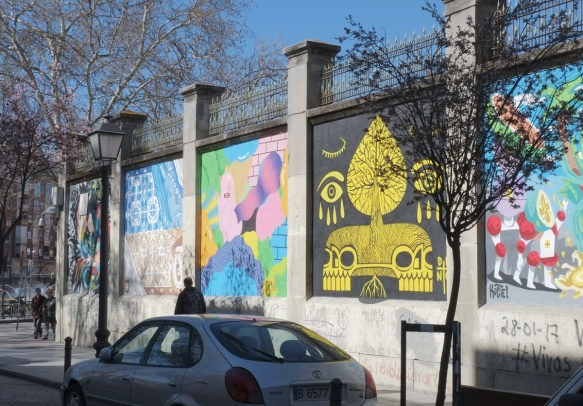 row of murals on a wall in Madrid
