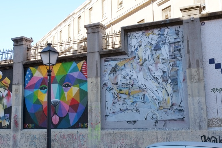 two murals, love wins by okuda and a piece by Laguna in pale turquoise and grey