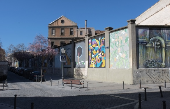 street scene in Madrid, murals on a high concrete wall, muros tabacalera,