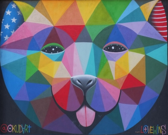 large animal face (bear?) in bright multi coloured triangles, by okuda (okudart)