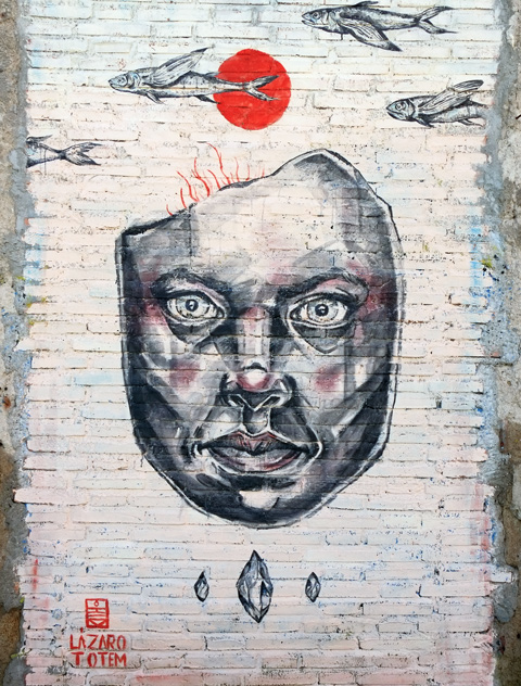 large realistic painting of a man's face on white brick wall, with some fish swimming above his head, signed as
