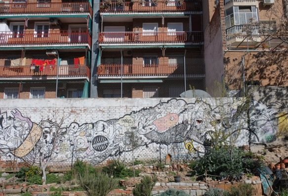 wall separating park from high rise apartment building with balconies, on wall is a mural