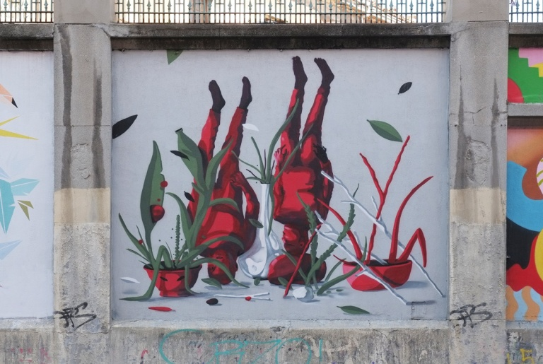 square mural, Madrid, muros tabacalera, 2 people all red, on their heads, along with two potted plants, one red and one green