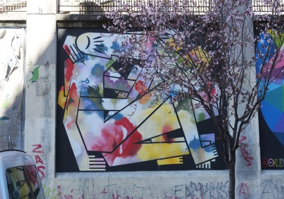 mural by Digo Diego of figures wrapped around each other, stylized, straight lines, blobs of colour, mural on a Madrid wall
