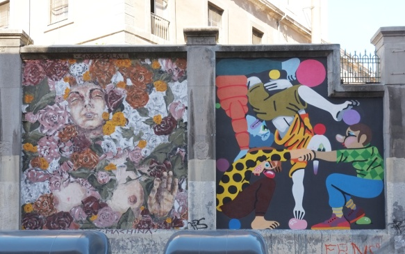 two street art murals side by side, one is cartoonish and the other is a realistic woman surrounded by flowers (covering her)