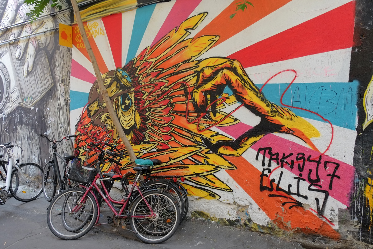 yellow, orange and blue mural of a bird and very large claw reaching for that bird