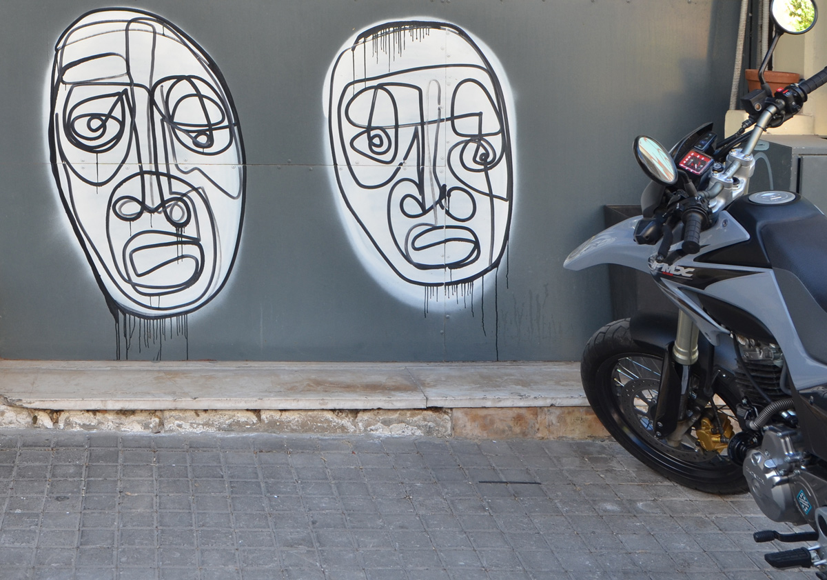 two large white ovals with faces drawn in black lines, one continuous line for each face. A motorbike is also in the picture