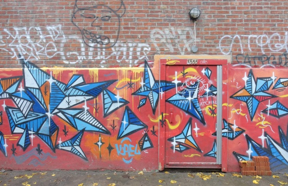 mural, red backgound across back of brick building and door, shapes made from blue triangles painted on the red
