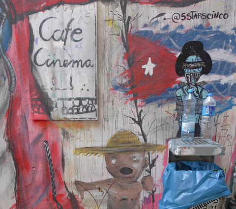 painted sign for cafe cinema, bear with a gold hat holding a red flag with a white star on it