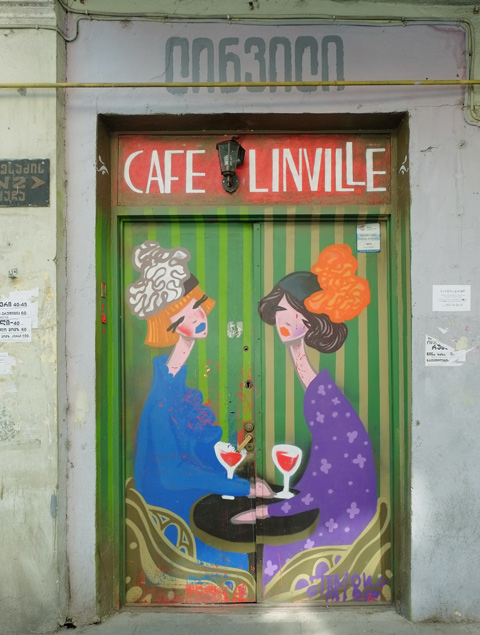 closed and locked double doors painted with two women talking over glasses of red wine, with the words Cafe Linville written across the top of the painting