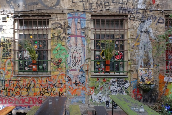 two windows on a wall, cafe tables in front of the wall, graffiti on the walls around the windows