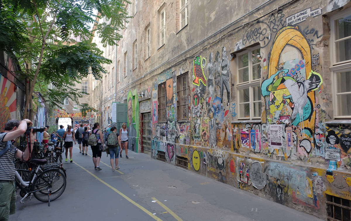 Cafe cinema courtyard in Berlin, one wall is covered with stencils, pasteups, stickers, and small street art, people walking past looking at it and taking picture of it