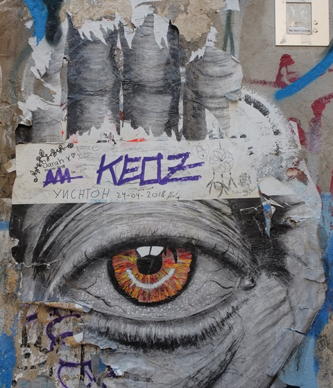 large paste up of black and white hand, large realistic looking eye, orange, in the middle of the palm
