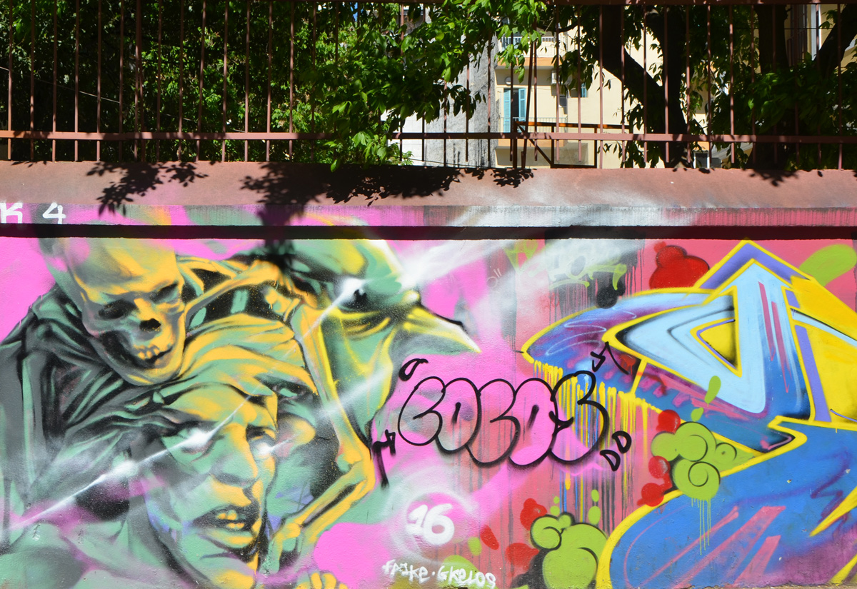 graffiti and street art on a low wall in Thessaloniki, with leaves of trees above the wall