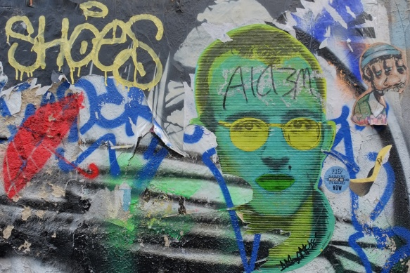 street art with a large bright bluish green man's face, with yellow sunglasses and dark green lips, also a stencil of a red umbrella