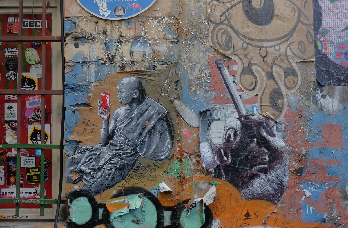 grey paper paste up of a bald man in seated position, drinking from a red and white coke can, lots of other graffiti around him including a large hand holding a cigarette