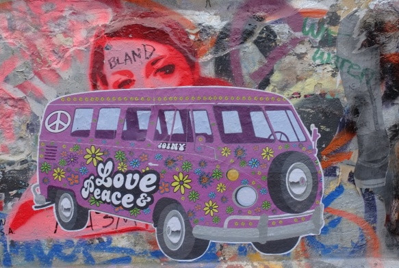 magenta VW microbus with flowers on it as well as words love and peace