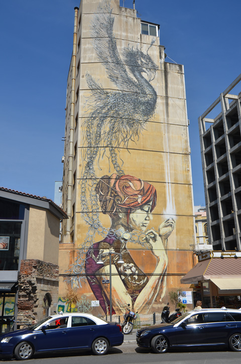 large mural on the side of abuilding, a woman in profile withher hair tied up, a feathery black bird above her