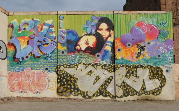 large colourful mural with the words love is life, a picture of a couple (heads) with flowers and hearts, also a handgun and bullet holes